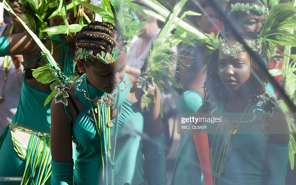 Young girls in costume take part on the first day of the Notting Hill Carnival in west London on August 25, 2013. Running over two days, the Caribbean carnival puts on a Kid's day on the Sunday when costume prizes are awarded and a 'main parade' day on the Monday. AFP PHOTO / WILL OLIVER