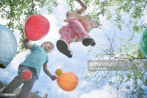 Young girls jumping on garden trampoline with balloons