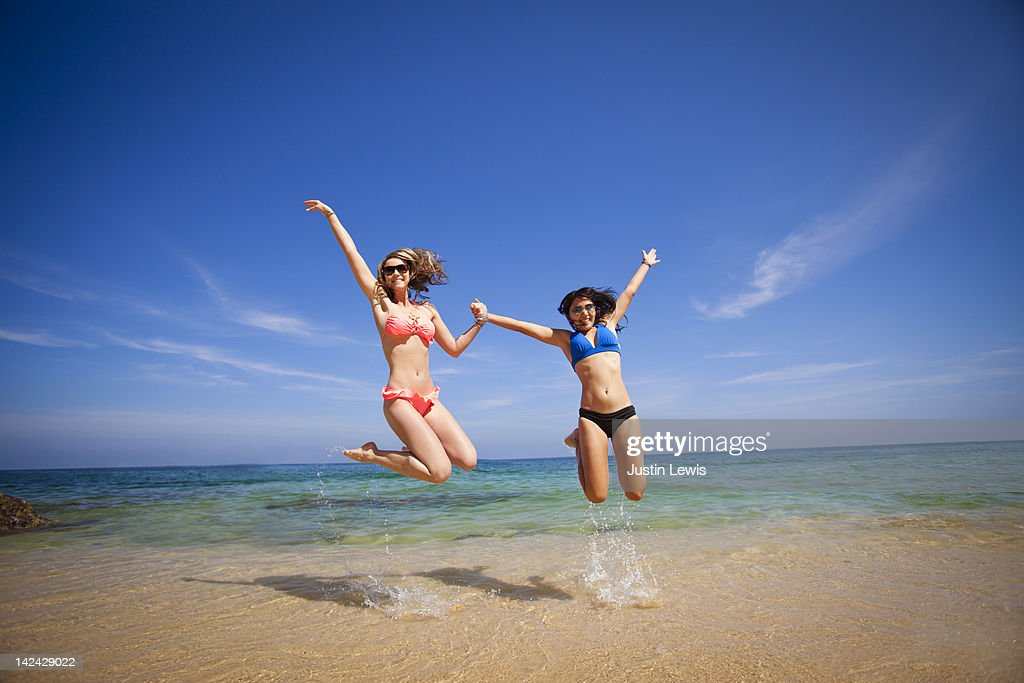 Young girls jumping & smiling in Sea of Cortez : Stock Photo