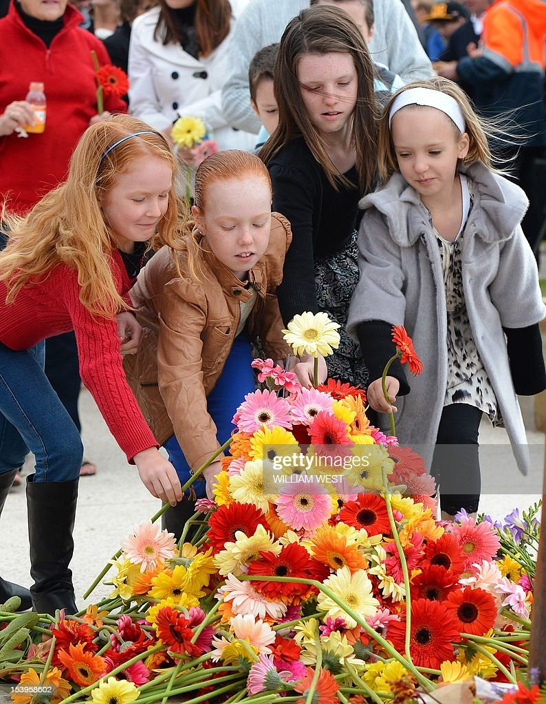 Young girls lay flowers after a ceremony to commemorate the 10th anniversary of the 2002 Bali attacks, at a memorial dedicated to Australians killed in the attacks, at Coogee Beach in Sydney on October 12, 2012. Survivors and relatives of the dead flocked to emotional Bali bombing ceremonies across Australia on October 12, with Foreign Minister Bob Carr praising the nation's mature response to the atrocity. AFP PHOTO/William WEST