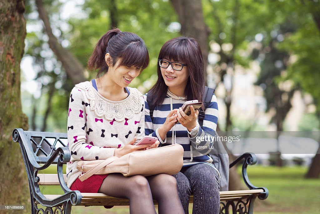 Young girls looking at smart phone : Stock Photo
