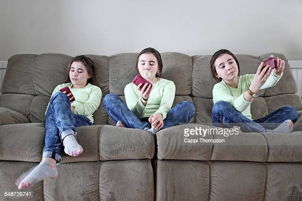 Young girls on couch with smart phones