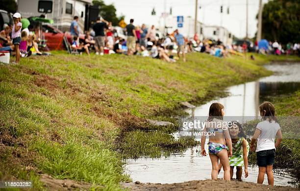 Young girls play in a drainage ditch as spectators camp out at a park in Titusville Florida as the space shuttle Atlantis prepares for launch from...