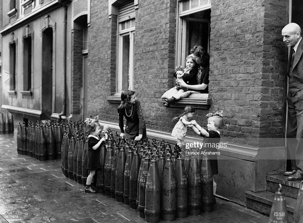 Young girls play with their dolls in a Munich street unhindered by the collection of shells in front of their house.