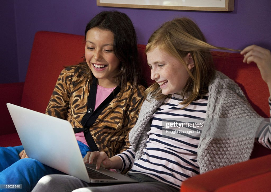 Young girls playing on computer together : Stock Photo