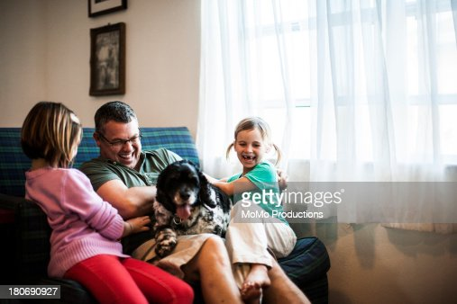 young girls playing with father and dog