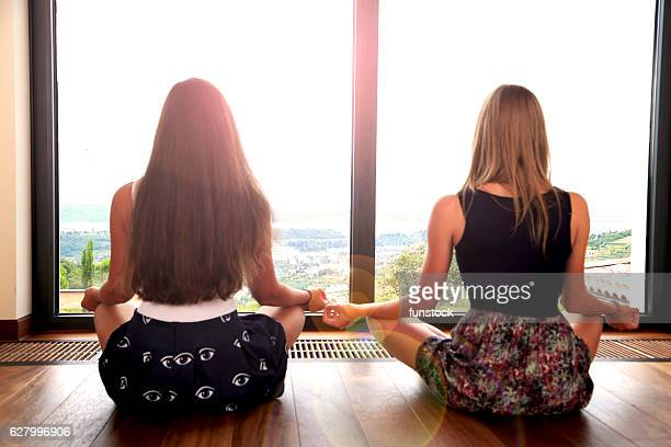 Young girls practising yoga by the window