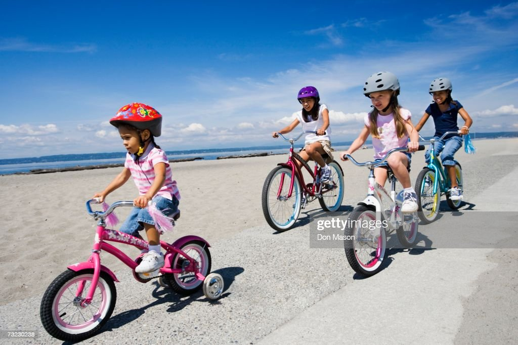 Young girls riding bicycles at beach