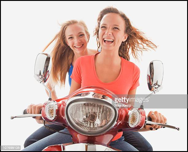 Young girls (16-17,16-17) riding scooter
