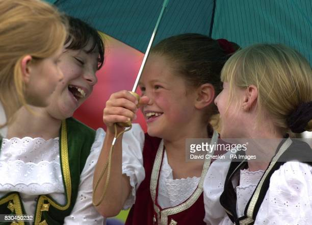 Young girls shelter from the rain during the Braemar Gathering held in Scotland The 183 year old Gathering features traditional Highland dancing...