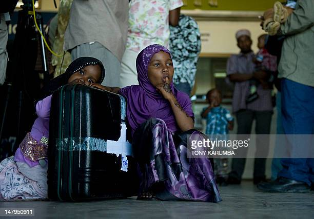 Young girls sit by their family's luggage at Zanzibar's Abeid amani Karume airport on July 6 after being repatriated from Somalia's capital Mogadishu...