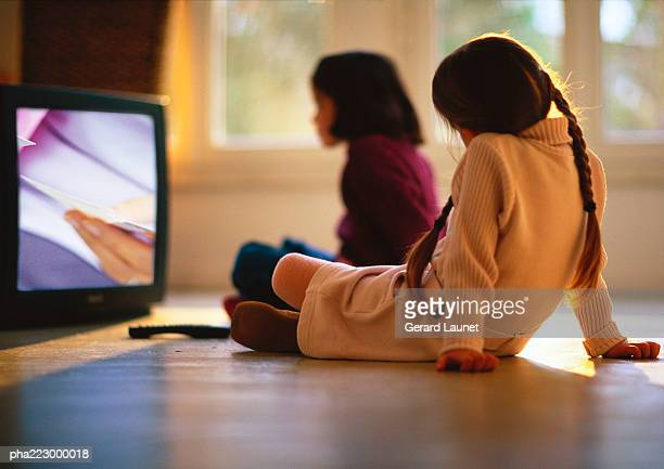 Young girls sitting on wood floor watching TV, girl in background blurred.