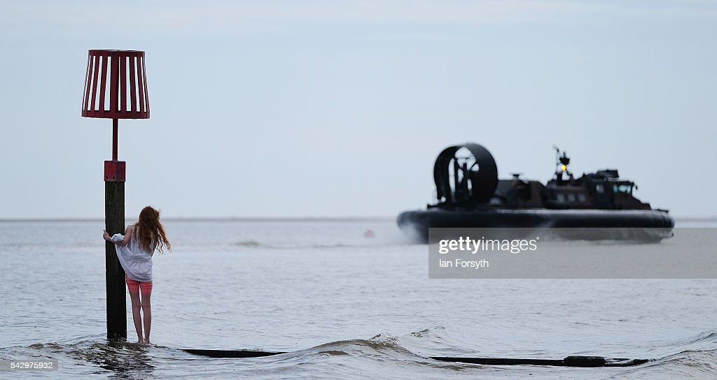 A young girls stands and watches as a hovercraft from the royal Marines heads out to sea after a beach assault during the Armed Forces Day National Event on June 25, 2016 in Cleethorpes, England. The visit by the Prime Minister came the day after the country voted to leave the European Union. Armed Forces Day is an annual event that gives an opportunity for the country to show its support for the men and women in the British Armed Forces.