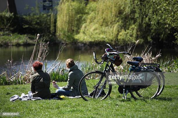 Young girls students are riding bicycle in Amsterdam Vondelpark