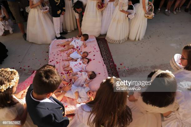 Young girls throw rose petals on babies during 'El Colacho' the 'baby jumping festival' in the village of Castrillo de Murcia near Burgos on June 18...