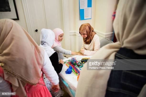 Young girls wait to have their hands painted with henna designs by Nada Ibrahim at an Eid alAdha celebration at the Alzahraa Arabic School in Portland