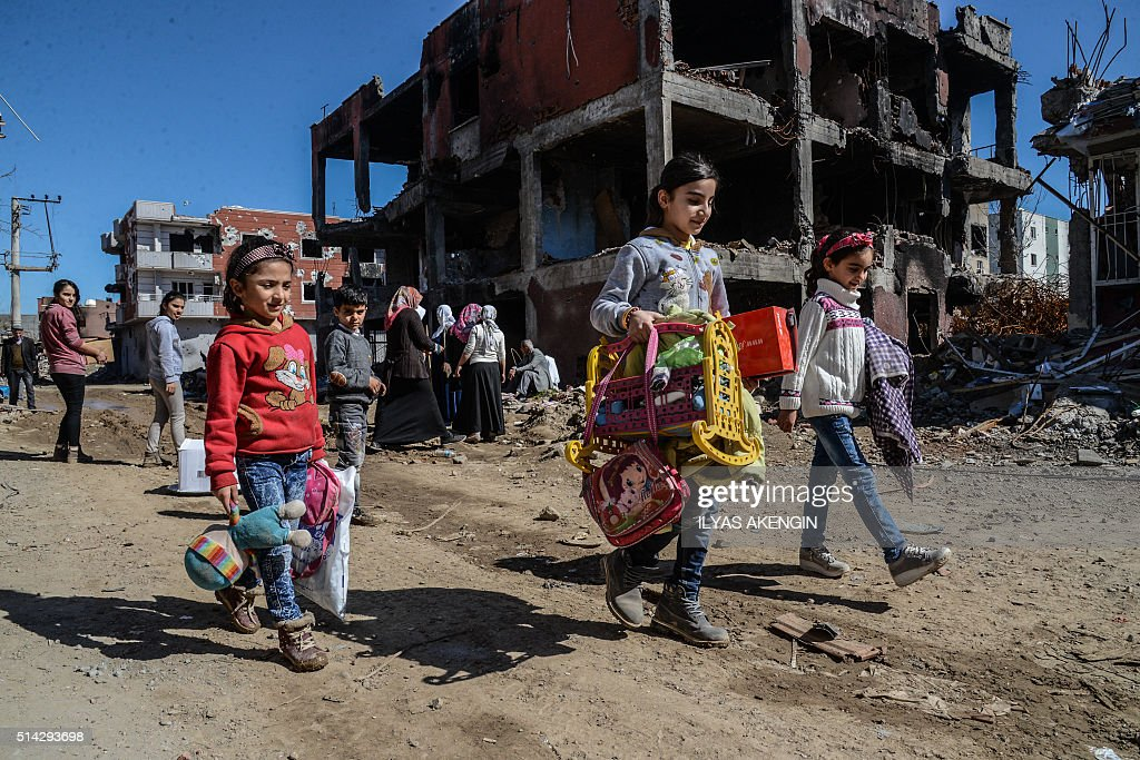 TOPSHOT Young girls walk next to ruined houses and shops on March 8 2016 during International Women's day in Cizre district Residents of Cizre in...