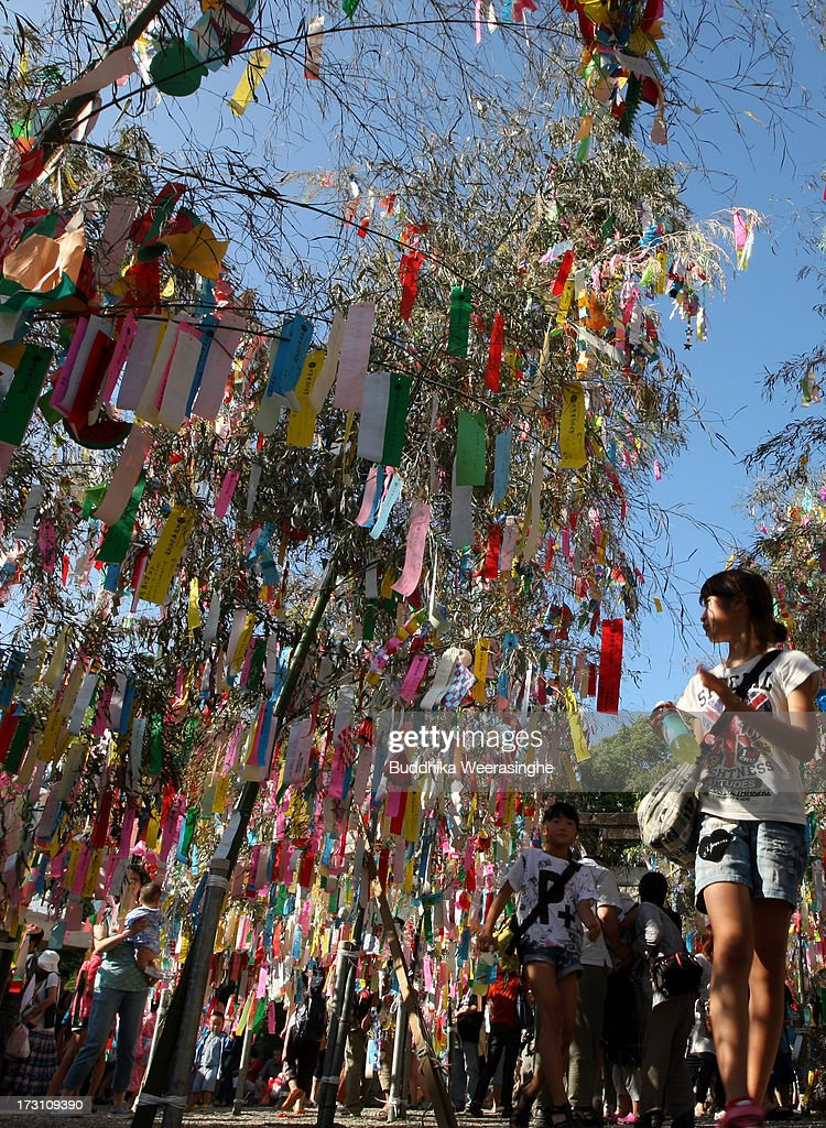 Young girls walk under the colorful paper strip decorations hung from bamboo branches during the Tanabata festival at the Hatamono shrine on July 7, 2013 in Osaka, Japan. Tanabata is a Japanese star festival in which people wear traditional ''yukata'' robes and write their wishes on strips of paper to hang on bamboo trees.