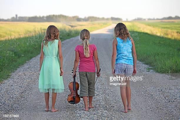Young Girls Walking Down Rural Gravel Road in Summer