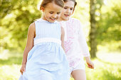 2 Young Girls Walking Through Summer Field Together