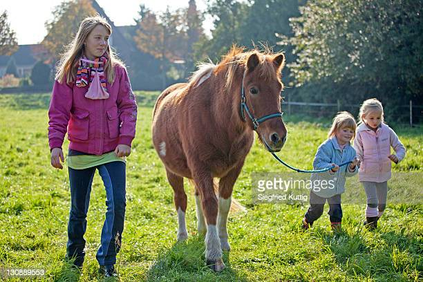 Young girls walking with a pony