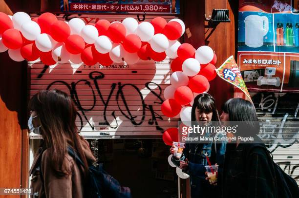 Young girls wearing masks walking down a street carrying soft drink on hand passing by colourful balloons