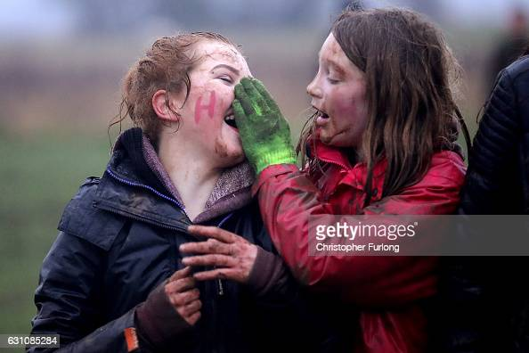Young girls wipe mud from their faces after wrestling in the fields for the hessian Hood during the junior Haxey Hood game at Haxey Village on...