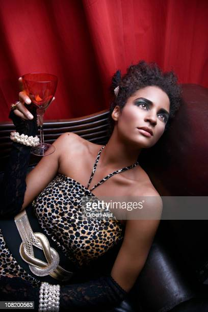 Young Glamourous Woman Lying on Couch Holding Glass