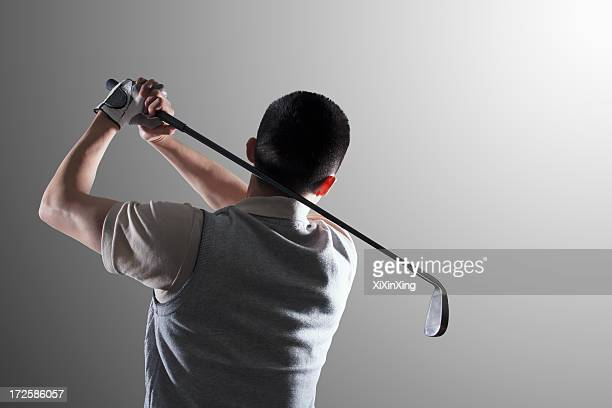 Young golf player swinging, rear view