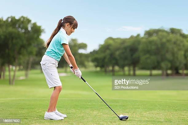Young golf player teeing off on course