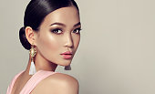 Young, gorgeous asian fashion-model put on in a smoky eyes style make up, black hair gattered in a beam. dressed in tassel earrings and  pink gown. Oriental beauty.