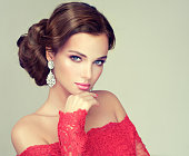 Young, gorgeous model put on in a delicate make up, and dressed in a red gown. Misty, romantic look. Wedding and evening style.