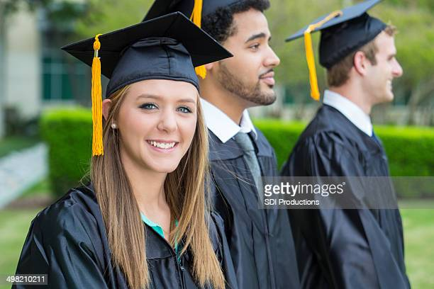 Young graduate smiling while waiting for diploma during graduation ceremony