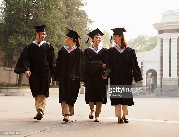 Young Graduates Walking Across Campus