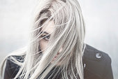 Young grey haired girl portrait in the wind with covered face