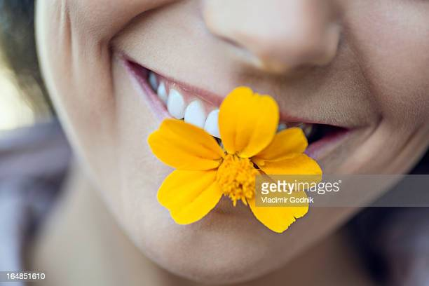 A young grinning woman holding a single flower in her mouth