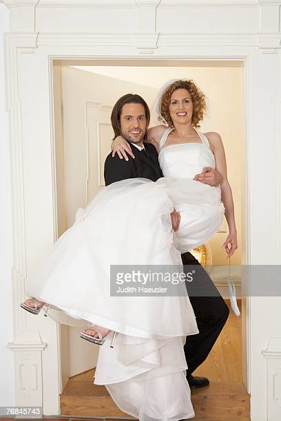 young groom carrying bride over threshold, portrait