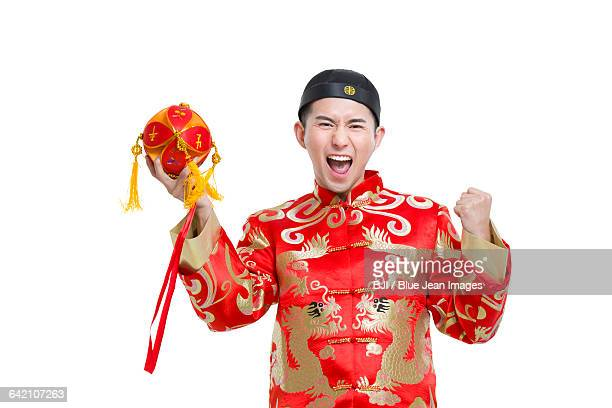 Young groom in Tang suit holding a embroider ball