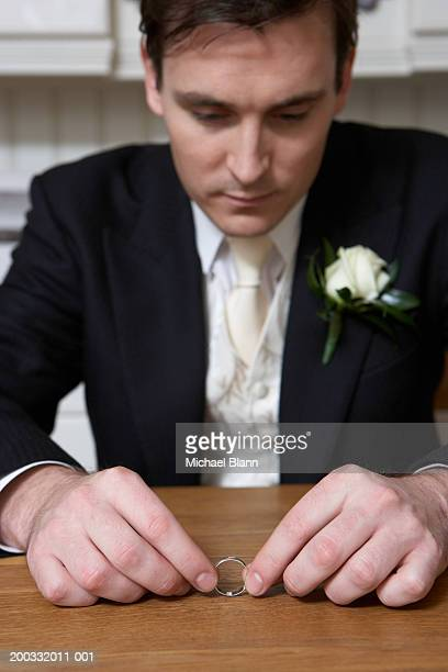 Young groom sitting at table toying with wedding ring, close-up