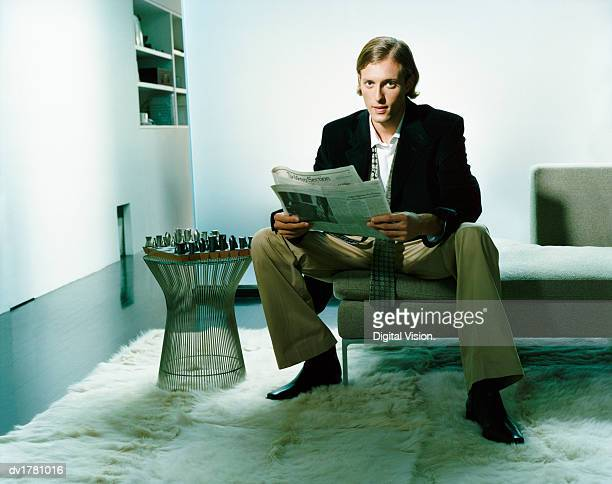 Young, Groomed Man Sits on a Sofa By a Side Table With a Chessboard, Reading a Newspaper