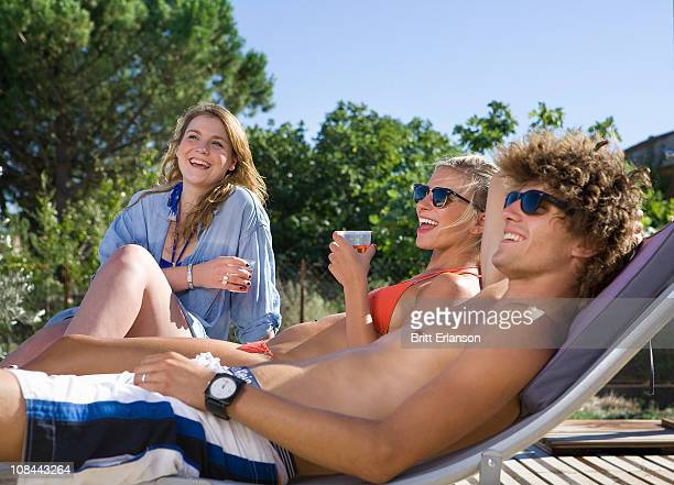 Young group drink, relax, laugh in sun