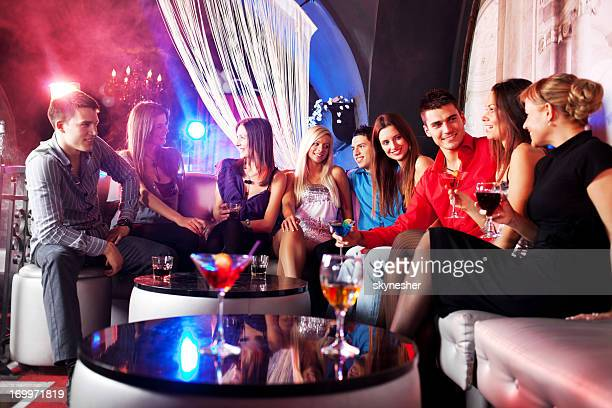 Young group of people sitting at the disco