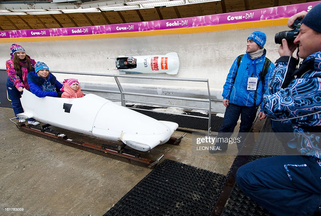 A young group sit in a bobsleigh during the Men's 2-man Bobsleigh event at the FIBT Bob & Skeleton World Cup at the Sanki Sliding Centre, some 50 km from Russia's Black Sea resort of Sochi, on February 16, 2013. With a year to go until the Sochi 2014 Winter Games, construction work continues as tests events and World Championship competitions are underway.