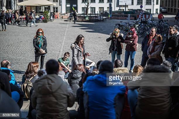 Young guide explains Copenhagen to tourists