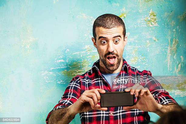 Young guy being shocked by a message on his smartphone