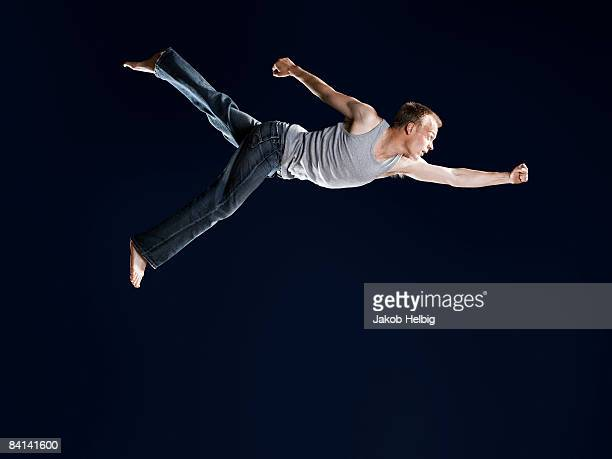 Young guy flying, running in mid air