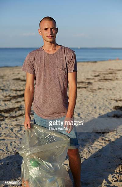 Young guy holding trash bag on beach