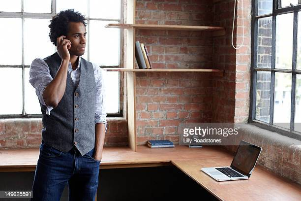 Young guy in new office talking on smart phone