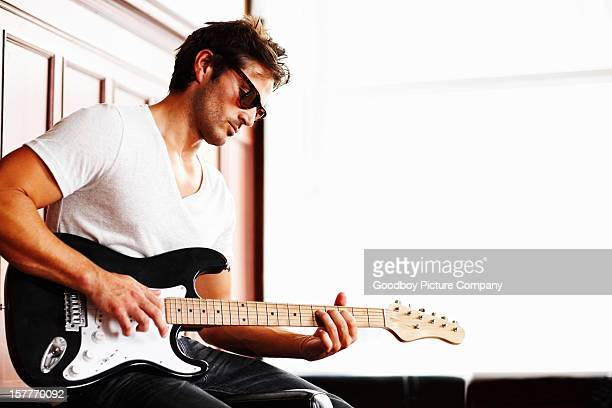 Young guy in sunglasses playing guitar