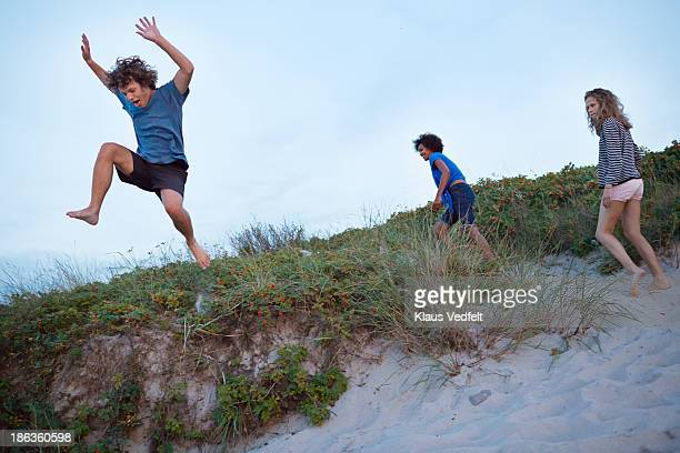Young guy jumping from sand dune